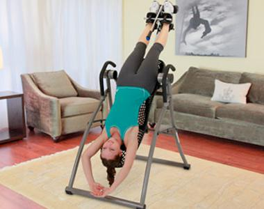 A woman exercising with an inversion machine